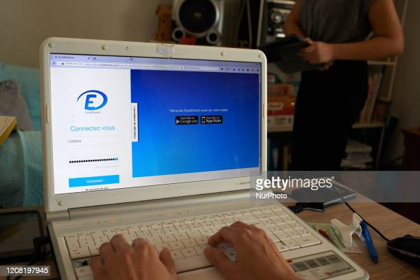 A schoolteacher prepares to connect to the website to be connected with her class exercices for her pupils For the 7th day French people are on...