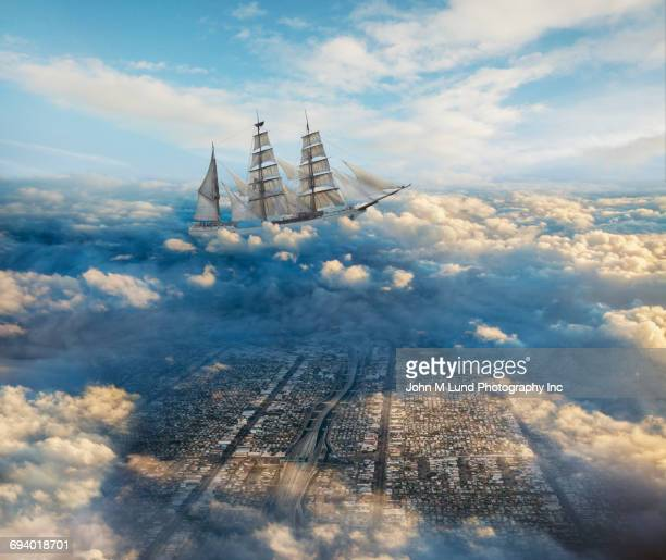 Schooner sailing in clouds above cityscape