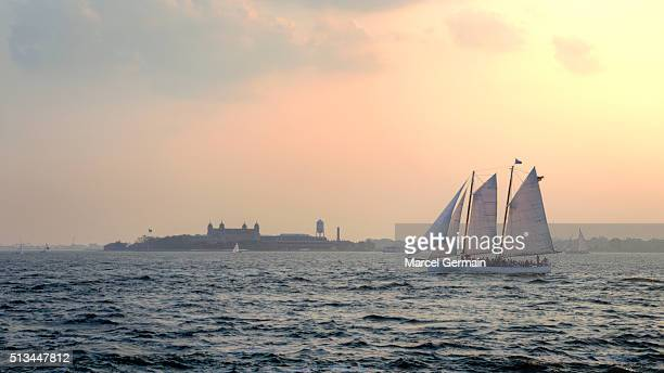 A schooner sails by Ellis Island in the sunset