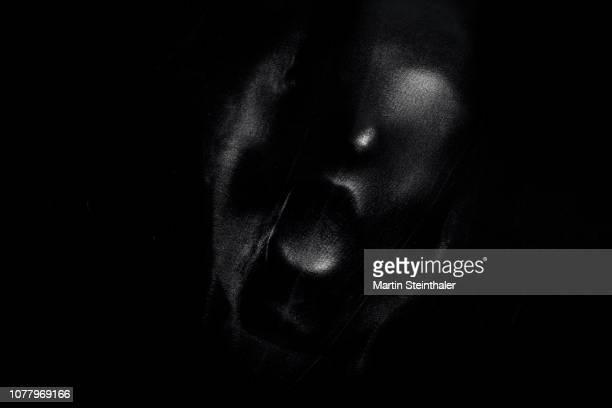 schreiendes gesicht hinter schwarzen latex stoff - latex photos et images de collection