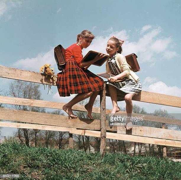 Schulmädchen mit Schiefertafeln auf einem Lattenzaun 50er Jahre