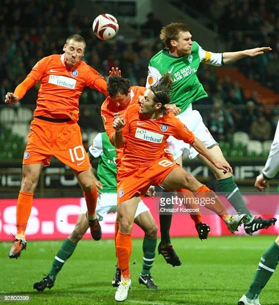 Schumacher and Matthias Hattenberger of Austria as well as Per Mertesacker of Bremen jump for a header during the UEFA Europa League Group L match...