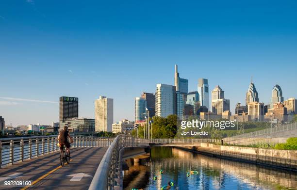 Schuylkill River Park Boardwalk with Cyclist and Philadelphia Skyline at Sunset