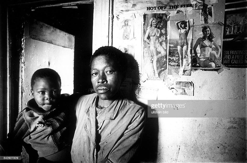 Schwarze Frau mit einem Kind auf dem Arm in einem Wohnghetto südwestlich vom Zentrum von Johannesburg- Juni 1976