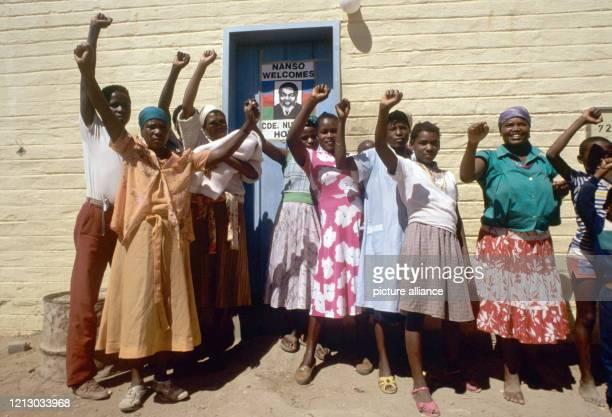 Schwarze stehen mit geballten Fäusten vor einem Plakat des SWAPOFührers Sam Nujoma aufgenommen im September 1989 in Katutura einem Township für...