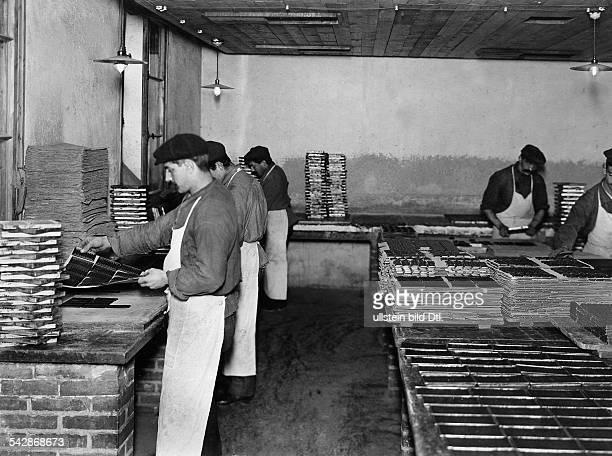 Schweiz Schokoladenfabrik KohlerArbeiter nehmen die fertigen Schokoladentafeln aus der Form undatiert um 1908Bild ist Teil einer Serie
