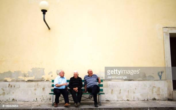 Scicli, Sicily: Three Senior Men On Bench; Yellow Wall