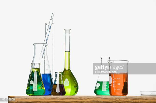 science beakers with liquid on table - beaker stock pictures, royalty-free photos & images