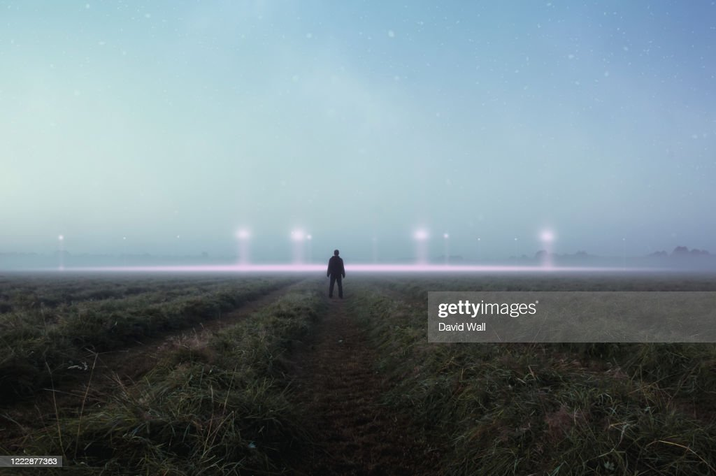 A science fiction concept. A man standing in a field back to camera looking into the sky, with glowing UFO orbs on the horizon : Stock Photo