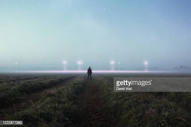 a science fiction concept. a man standing in a field back to camera looking into the sky, with glowing ufo orbs on the horizon - mystery stock pictures, royalty-free photos & images