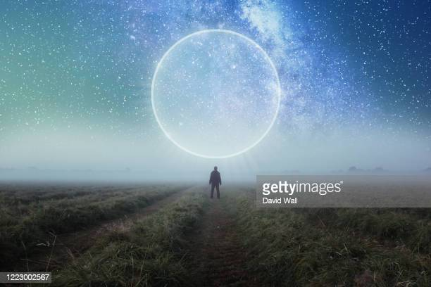 a science fiction concept. a man standing in a field looking out across space with a glowing portal in the night sky - star space stock pictures, royalty-free photos & images