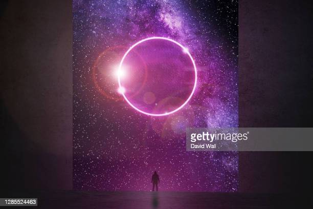 science fiction concept. of a figure standing in a gap in a wall. looking at a bright glowing portal against a galaxy of stars. - star space stock pictures, royalty-free photos & images