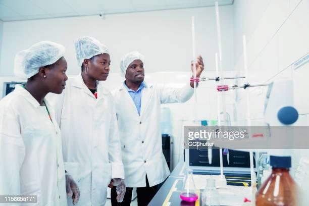 研究室のインストラクターの指導を聞く科学インターン - ザンビア ストックフォトと画像