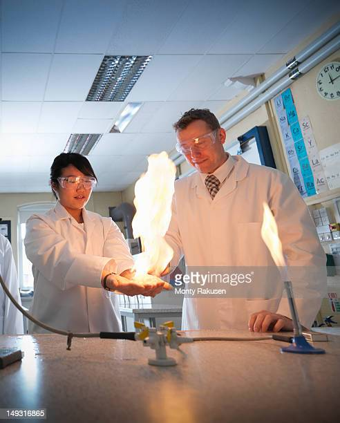 science teacher and student conducting experiment in school laboratory - hot teacher stock pictures, royalty-free photos & images