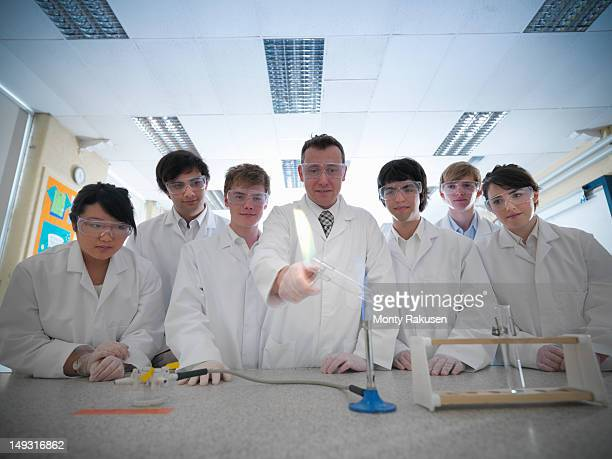 Science teacher and students conducting experiment in school laboratory