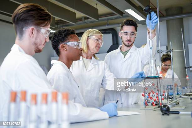Science teacher teaching young chemistry students in laboratory