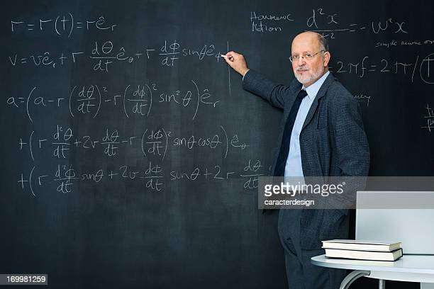 Science teacher writting at blackboard physics equation