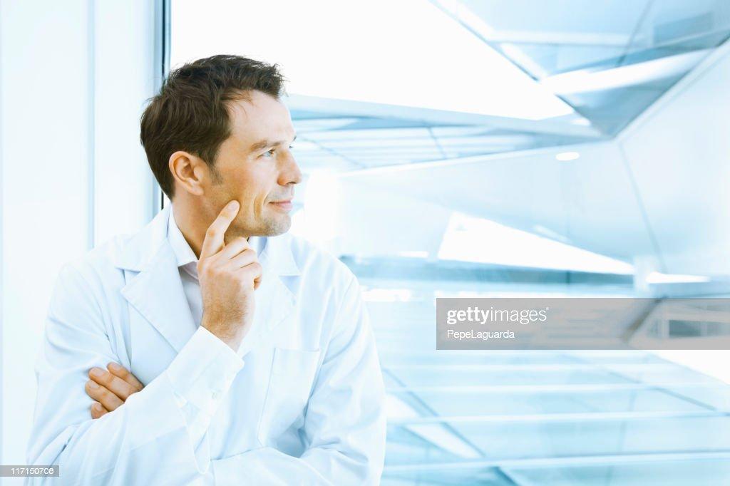 Científicos en labcoat mirando a través de la ventana : Foto de stock