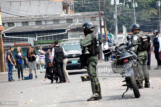 Scientific Police personnel collect evidence after a protest against Venezuelan President Nicolas Maduro in San Cristobal Venezuela on March 29 2016...