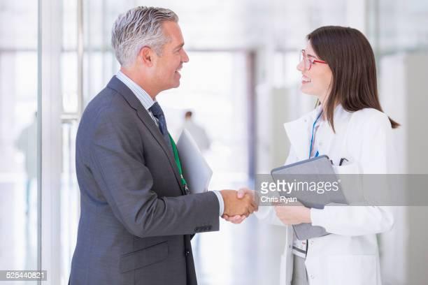 Scientist and businessman shaking hands in hallway