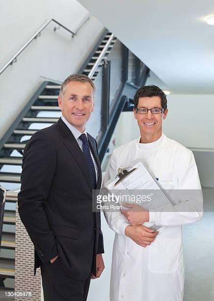 Wissenschaftler und Geschäftsmann lächelnd im Büro