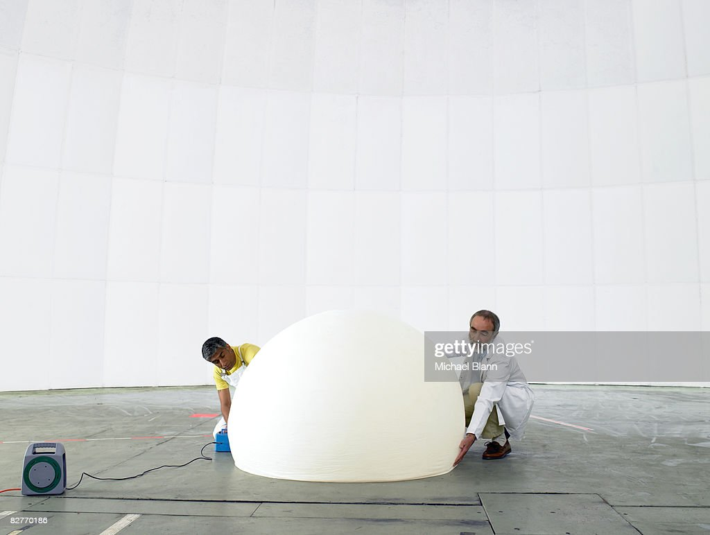 Scientist and engineer inflate weather balloon : Stock Photo