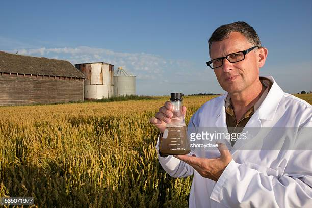 Scientist and Farm with Barns conducting an Experiment in Wheatfield