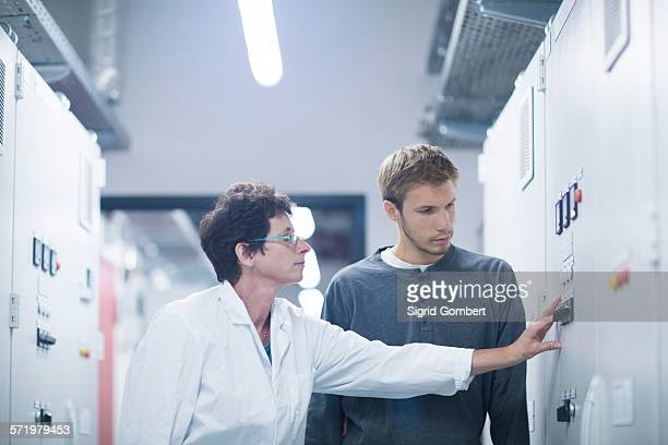 Scientist and technician pressing switch in technical room