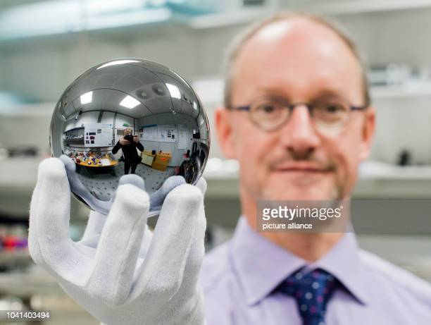 Scientist Arnold Nicolaus holds a silicon sphere which weighs exactly one kilogram at the PhysikalischTechnische Bundesanstalt in Braunschweig...
