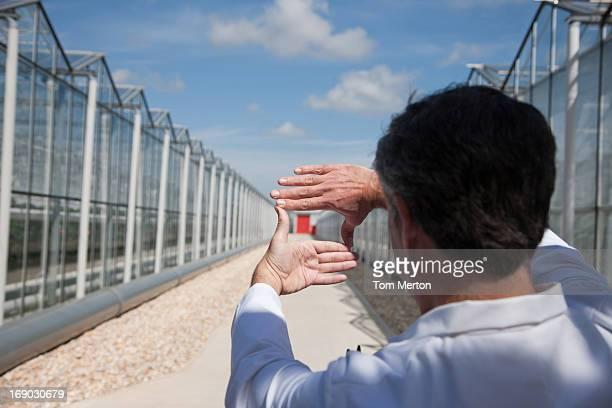 Scientist between greenhouses