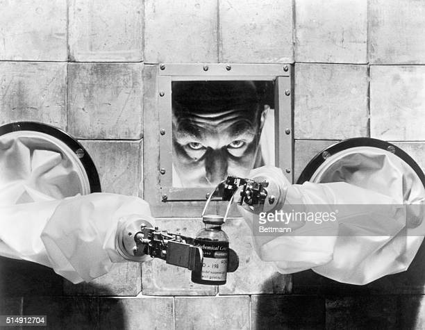 A scientist carefully bottles isotopes with robotic arms from behind a protective wall at the Radiochemical Centre one of the largest pharmaceutical...