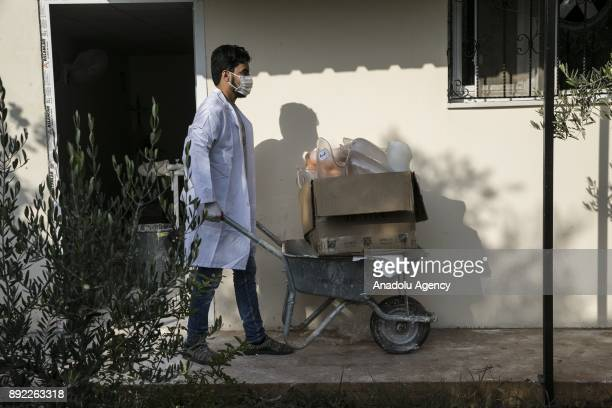 A scientist carries a box of prosthetic legs after they prepared for Syrians who lost their upper and lower extremities due to the ongoing civilwar...
