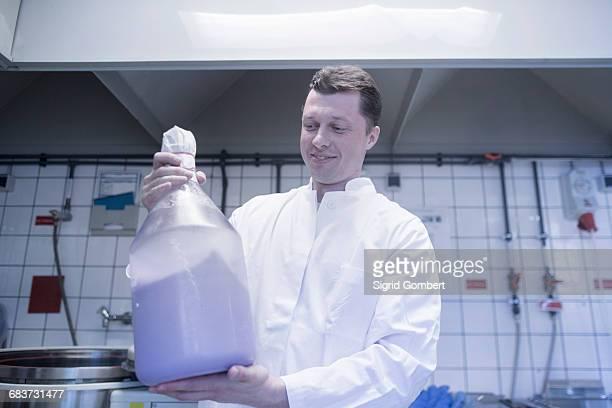 scientist carrying large bottle of chemical in laboratory - sigrid gombert imagens e fotografias de stock