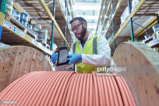 Scientist checking electrical cable with radioactive source equipment in cable store