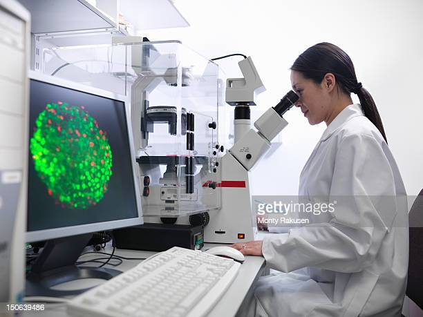 Scientist conducting stem cell research on a confocal microscope in biolab