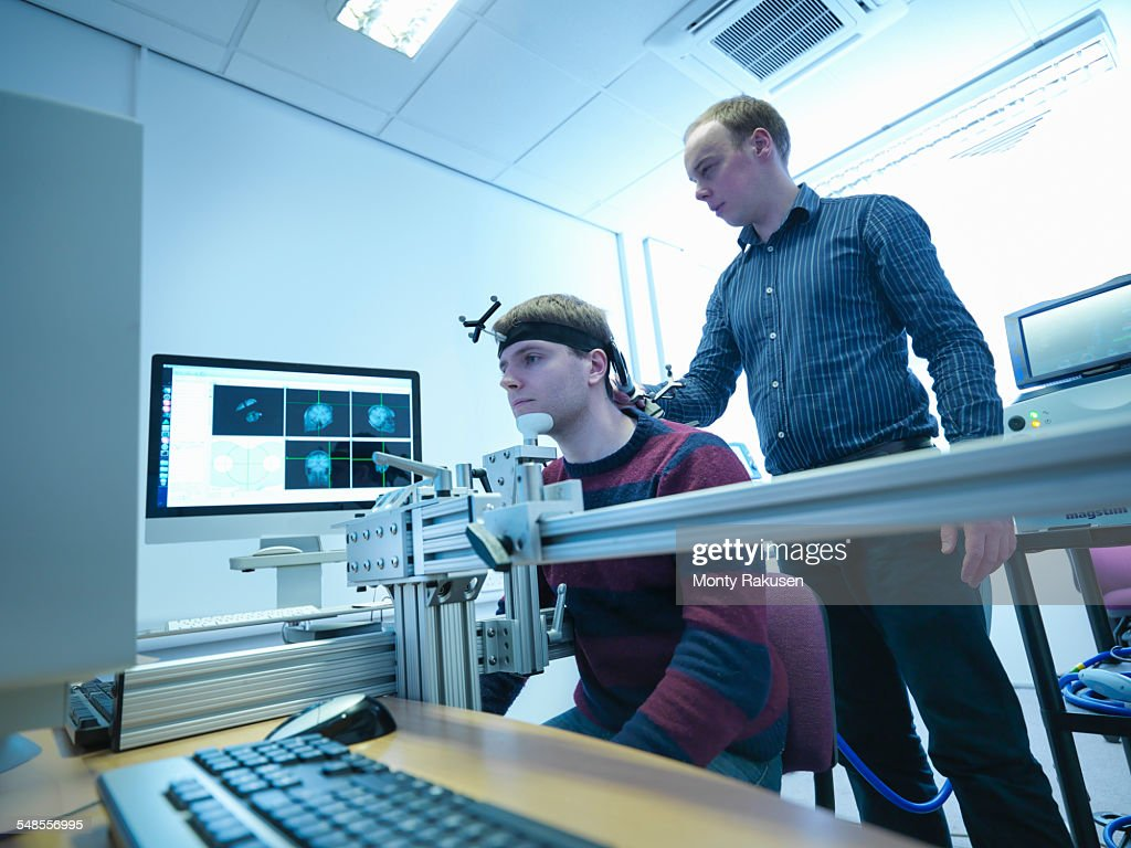 Scientist conducting transcranial magnetic stimulation (TMS) experiment on patient : Stock Photo