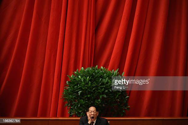 Scientist delegate yawns at stage during the closing session of the 18th National Congress of the Communist Party of China inside the Great Hall of...