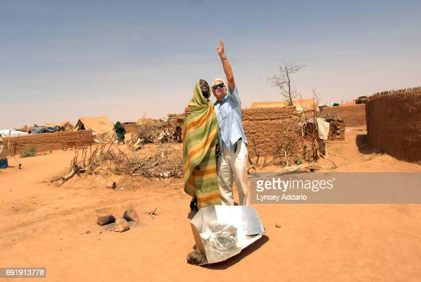 Scientist Derk Rijks from the Netherlands shows a Sudanese refugee how to align her solar stove with the sun while volunteering in Iridimi camp in...
