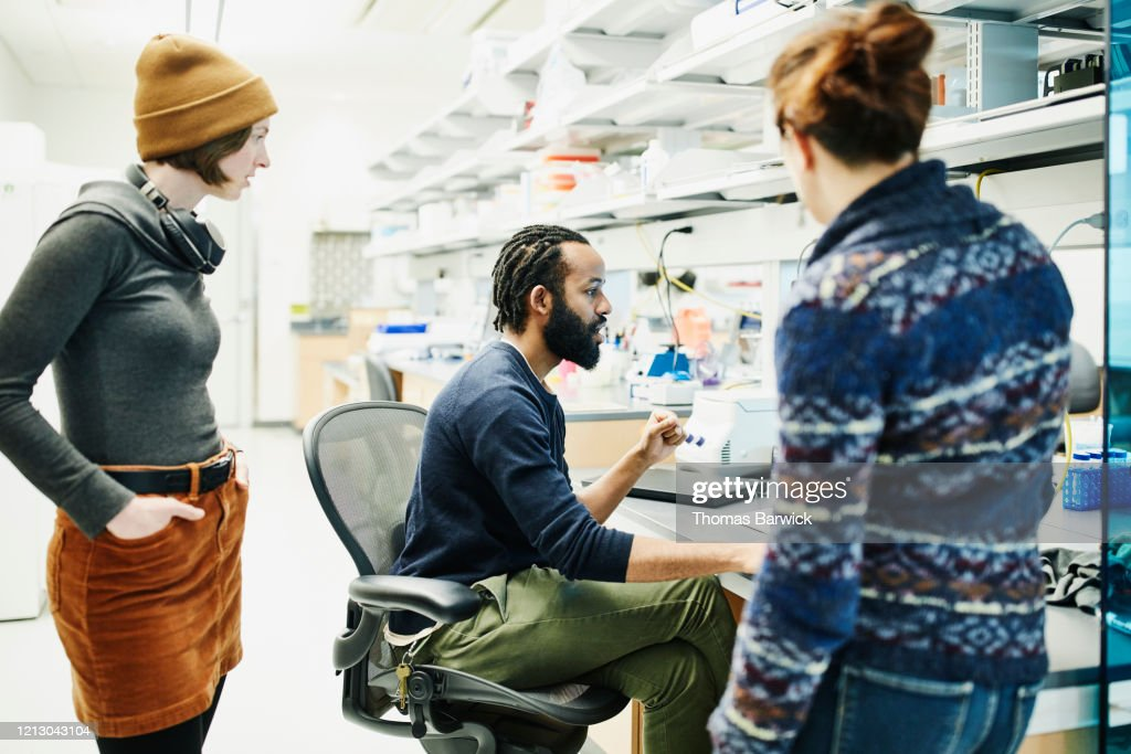 Scientist discussing data with colleagues while working in research lab : Stock Photo