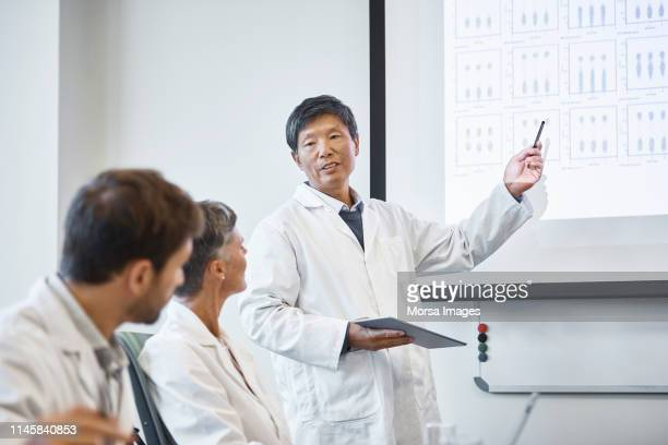 scientist discussing over records with colleagues - medical research stock pictures, royalty-free photos & images
