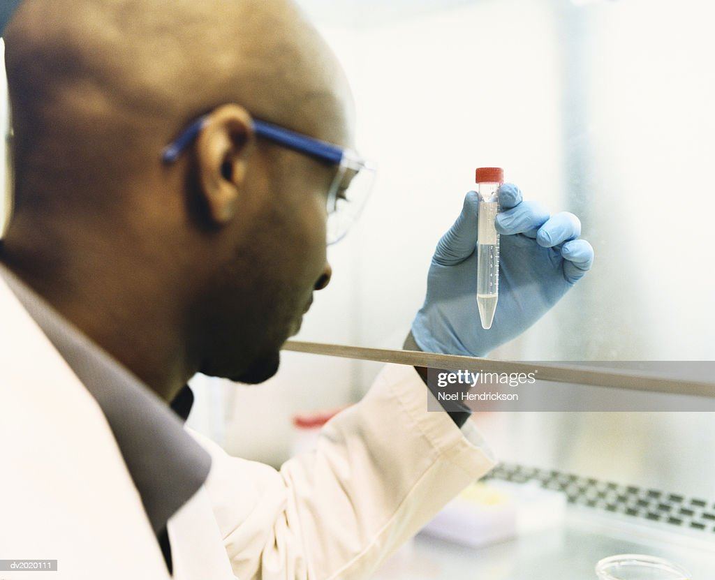 Scientist Examining a Container : Stock Photo
