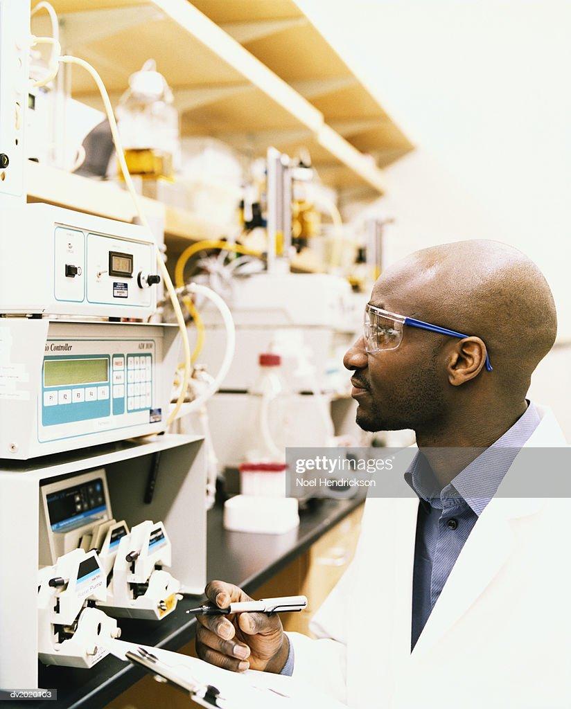 Scientist Examining a Machine : Stock Photo