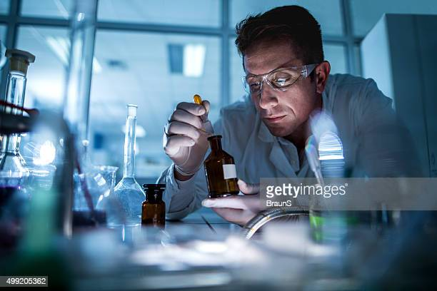 Scientist examining chemical substances in a laboratory.