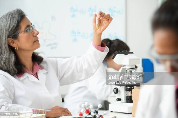 scientist examining liquid in vial - scienziata foto e immagini stock