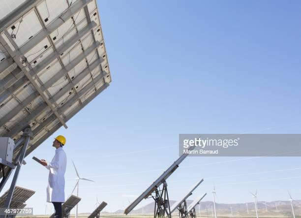 Cientista examinando painel solar na paisagem rural