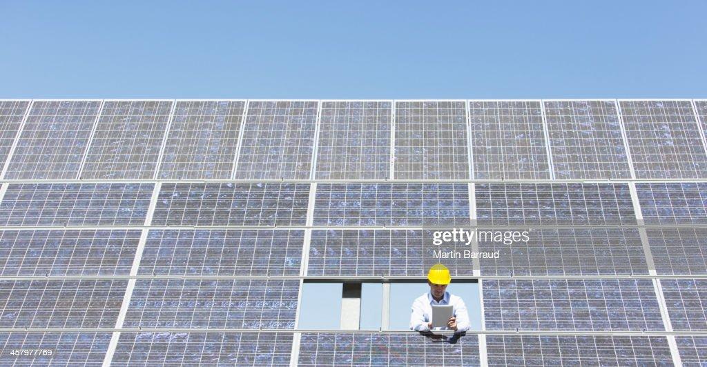 Scientist examining solar panel in rural landscape : Stock Photo
