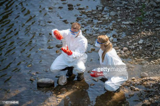 scientist examining toxic water samples - water pollution stock pictures, royalty-free photos & images
