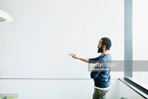 scientist explaining data on whiteboard in conference room - concept stock pictures, royalty-free photos & images