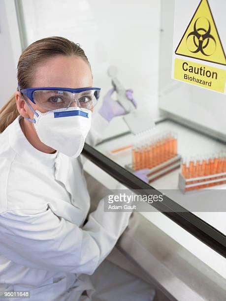 Scientist filling test tubes under biohazard sign