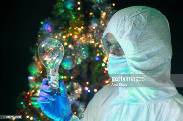 scientist gazes at a light bulb that he holds in his hand. christmas tree in the background. - inventor stock pictures, royalty-free photos & images